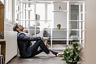 Exhausted businessman sitting on the floor - KNSF01327