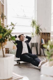 Smiling businessman sitting on skateboard - KNSF01333