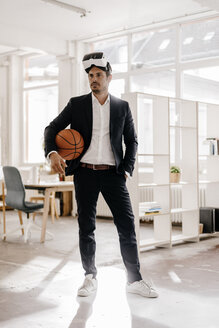 Businessman wearing VR glasses holding basketball in office - KNSF01336