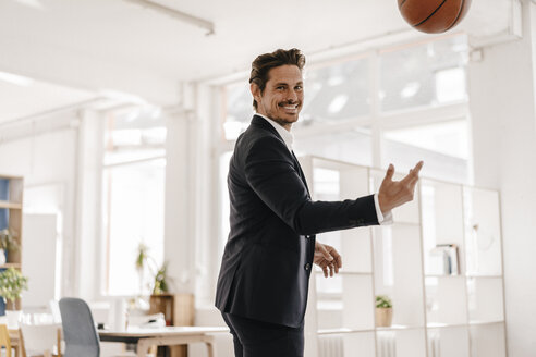 Businessman playing basketball in office - KNSF01339
