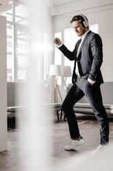Passionate businessman listening to music on headphones - KNSF01342