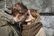 Young couple sharing earbuds kissing at stone wall - ANHF00033