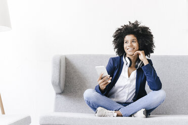Young businesswoman using smartphone with headset - KNSF01349