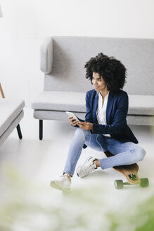 Young businesswoman using smartphone with headset - KNSF01352