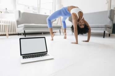 Young woman practising yoga with laptop by her side - KNSF01358