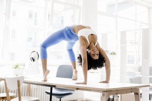 Young woman practising yoga on her desk - KNSF01379
