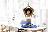 Young woman practising yoga on her desk - KNSF01382