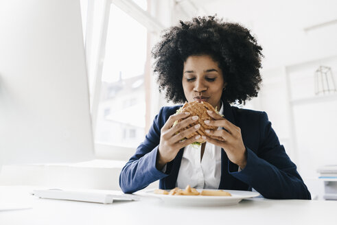 Young businesswoman eating hamburger at her desk - KNSF01388