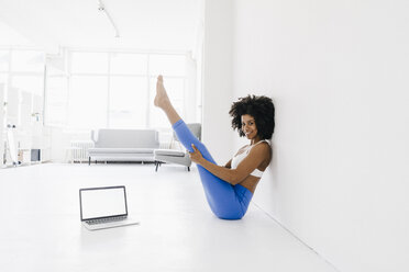 Young woman practising yoga with laptop by her side - KNSF01406