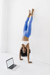 Young woman practising yoga with laptop by her side - KNSF01409