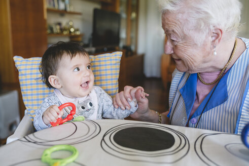 Great-grandmother playing with a baby girl sitting in the high chair next to the table with toys - GEMF01623