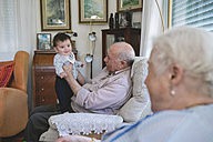 Happy Baby girl standing with help of Great-grandfather at home - GEMF01626