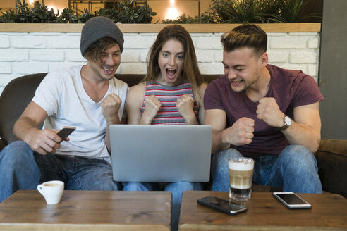 Three excited friends looking at laptop in a cafe - KKAF00815