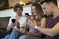 Three friends using their cell phones in a cafe - KKAF00818