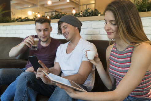 Three friends using tablet and cell phone in a cafe - KKAF00821