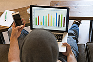 Young man using cell phone and laptop with bar chart in a cafe - KKAF00824