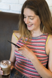 Happy young woman using cell phone in a cafe - KKAF00827