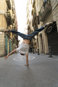 Young man doing a handstand in the city - KKAF00851