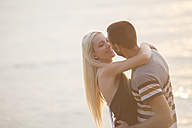 Rpmantic couple embracing by the sea - ZOCF00390