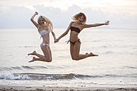 Two young women having fun on the beach - ZOCF00399