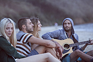 Four friends at the beach making music - ZOCF00408