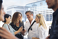 Group of happy casual businesspeople sharing cell phone on urban square - ZEF13707