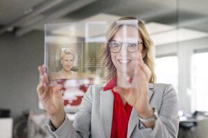 Businesswoman communicating via futuristic portable device - PESF00587
