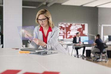 Businesswoman using futuristic portable device - PESF00590