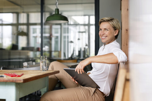 Happy blond woman with tablet sitting at table - PESF00599