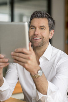 Smiling businessman using tablet - PESF00605