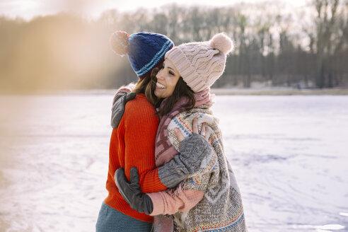 Friends hugging on frozen lake - MFF03532