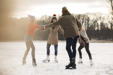 Friends ice skating in a circle on frozen lake - MFF03535