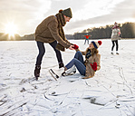 Man helping ice skating woman up on icy surface of frozen lake - MFF03541