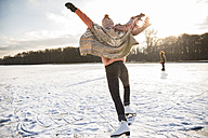 Rear view of woman with ice skates on frozen lake - MFF03550