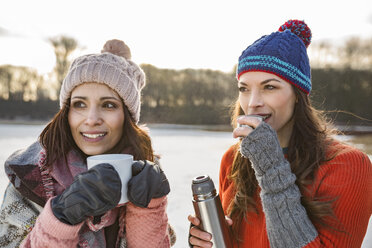 Two women drinking hot beverages outdoors in winter - MFF03559