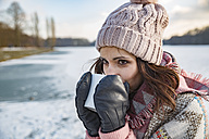Woman drinking hot beverage from a cup outdoors in winter - MFF03562
