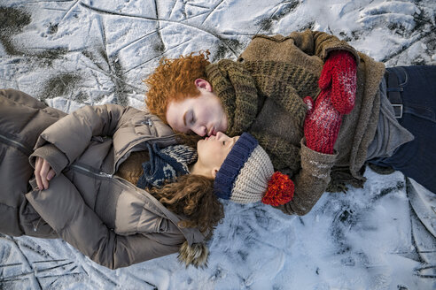 Couple lying down on frozen lake surface kissing - MFF03565