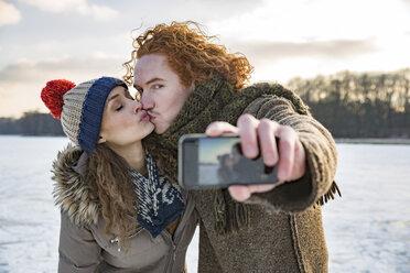 Couple kissing on frozen lake taking a selfie - MFF03568