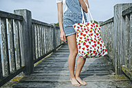 Woman standing on boardwalk holding beach bag, partial view - KIJF01501