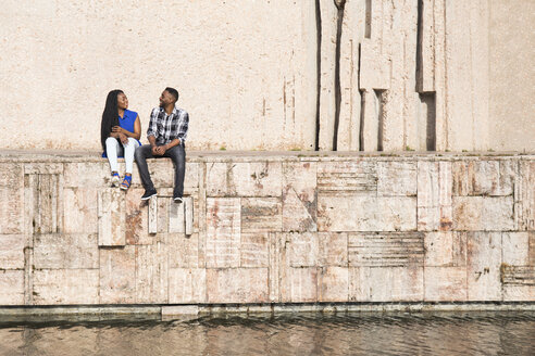 Talking young couple sitting on a wall near water - ABZF02030