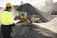 Worker standing at quarry, using clipboard - ZEF13734