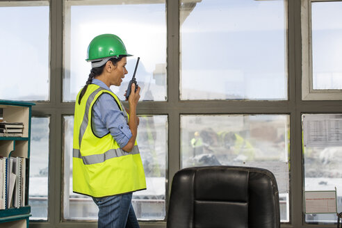 Female quarry worker standing in site office talking on radio device - ZEF13752