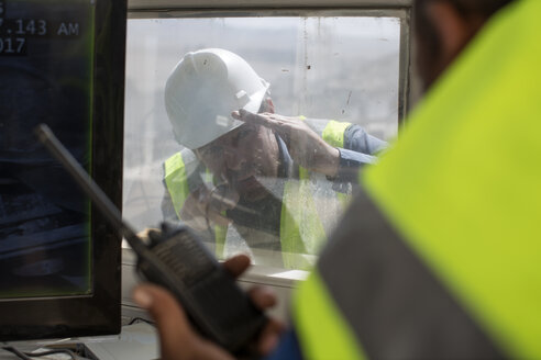 Workers at quarry, one holding radio device - ZEF13758