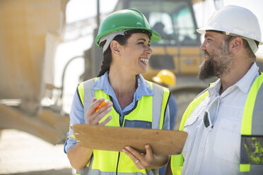 Male and female quarry workers discussing on site - ZEF13761