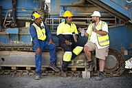Colleague workers at quarry sitting on machine, taking a break - ZEF13779