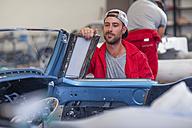 Mechanics restoring vintage cars in workshop - ZEF13806