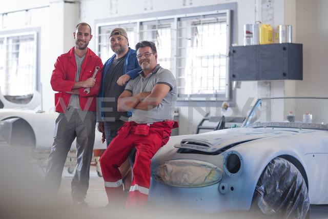 Car mechanics together in car restoration workshop - ZEF13812