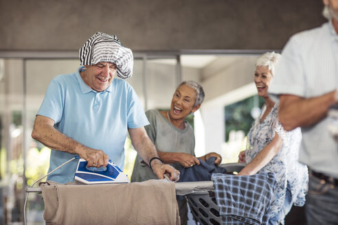 Seniors ironing clothes together having fun - ZEF13827