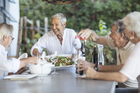 Smiling senior woman serving lunch on terrace - ZEF13842