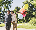 Happy senior couple with balloons in a park - UUF10644